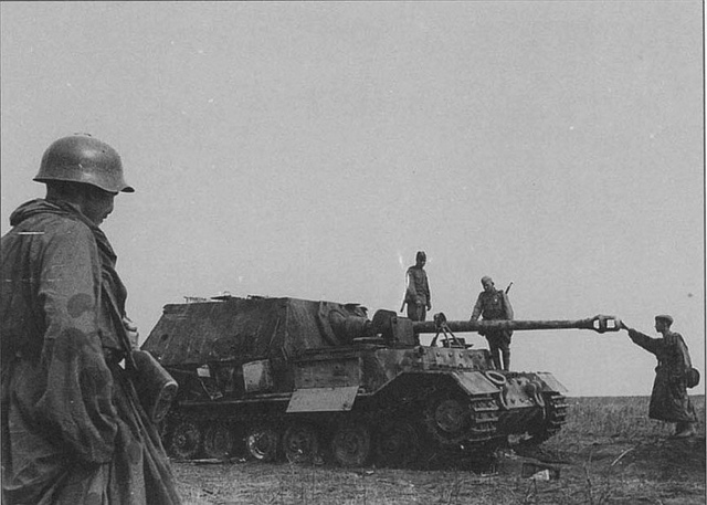 Soviet soldiers inspect lined during the Battle of Kursk German heavy self-propelled artillery class fighter tank